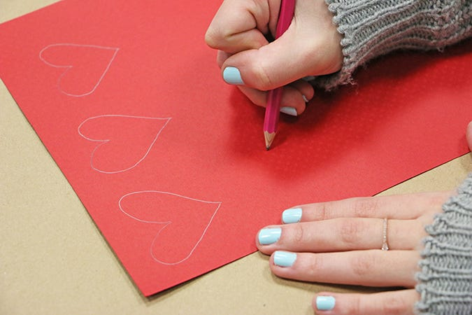 drawing hearts on red paper